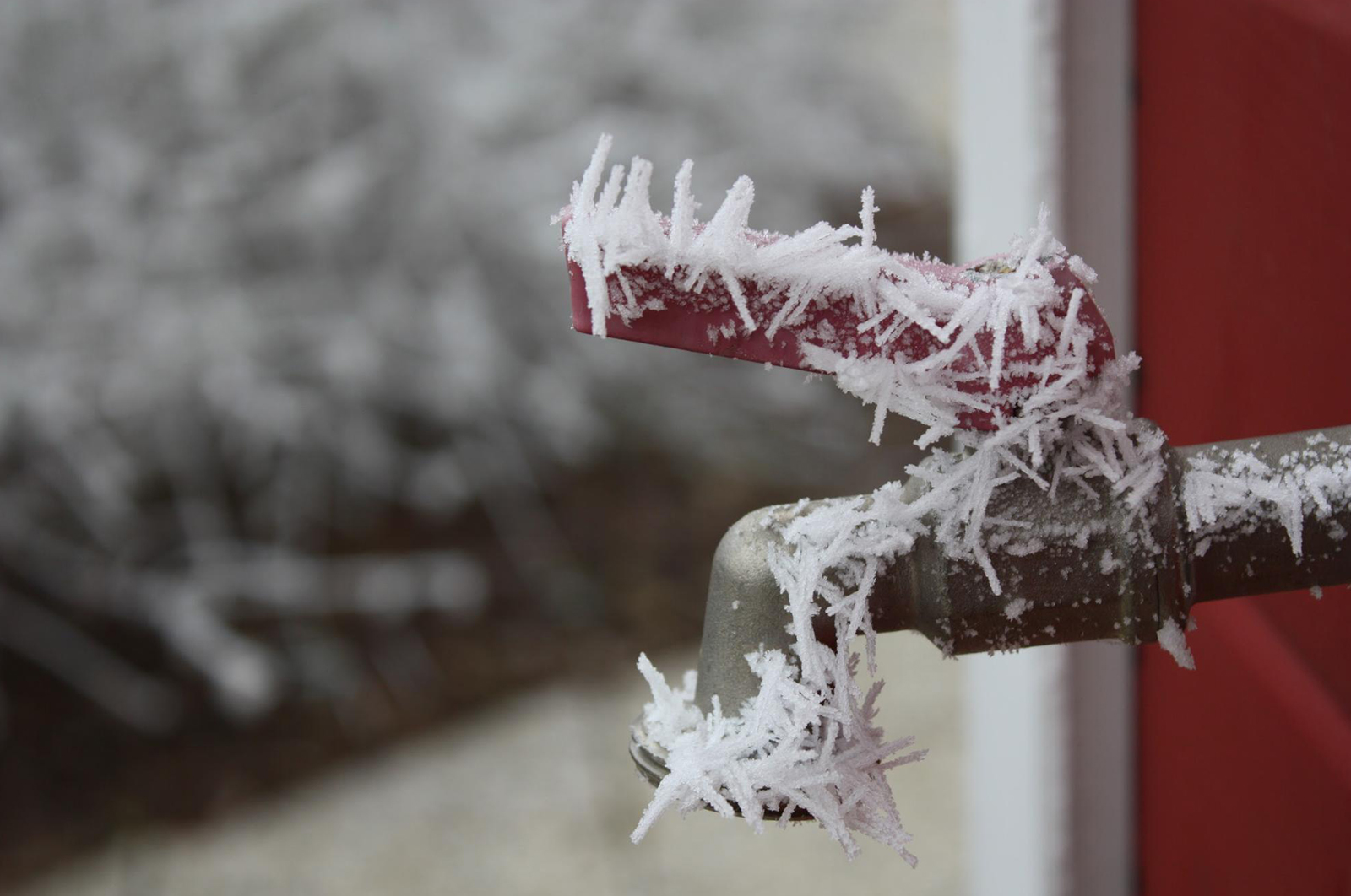 Closeup of frozen faucet with icicles forming around it