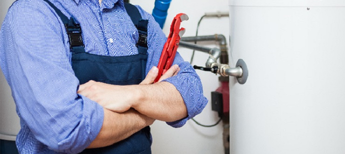 Cropped photo of a plumber standing beside a water heater